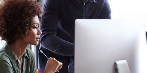Young creative professionals working together at a computer in an office, vertical, close up